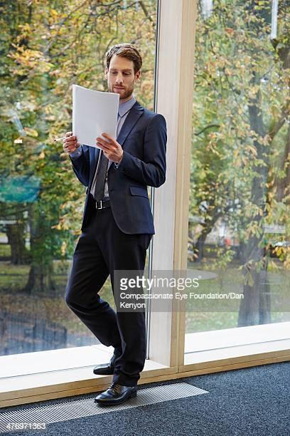 Businessman reading document leaning on window