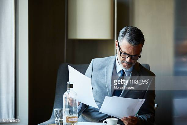 businessman reading documents in hotel room - elegantie stockfoto's en -beelden