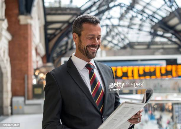 Businessman reading financial newspaper before business trip
