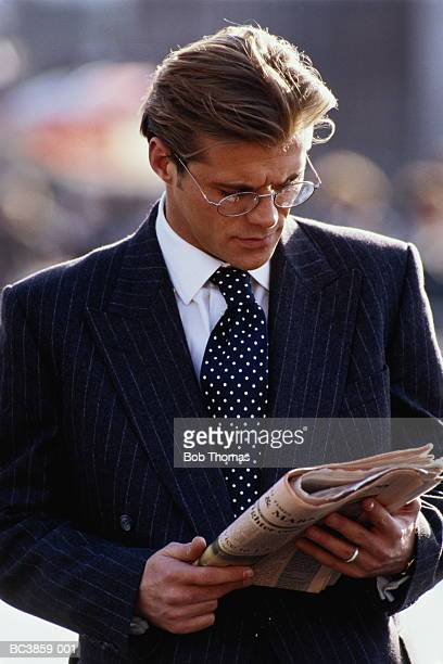 Businessman reading financial newspaper, outdoors, close-up