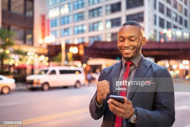 businessman reading good news on mobile phone in downtown chicago - mlenny stock pictures, royalty-free photos & images