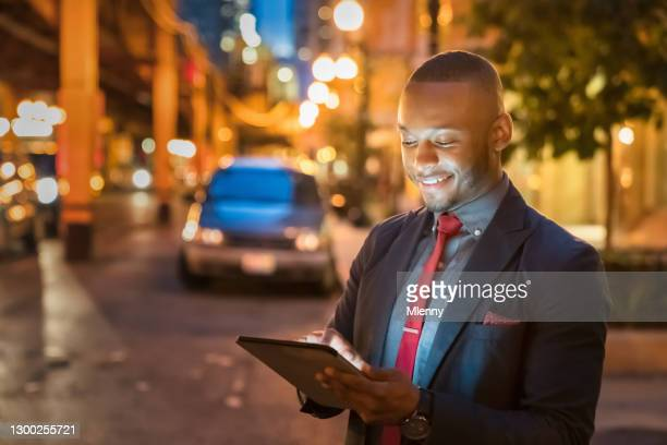 businessman reading messages on 5g digital tablet computer in chicago - mlenny stock pictures, royalty-free photos & images