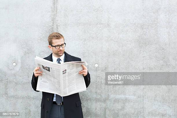 Businessman reading newspaper at concrete wall