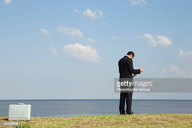 Businessman reading newspaper by ocean, rear view