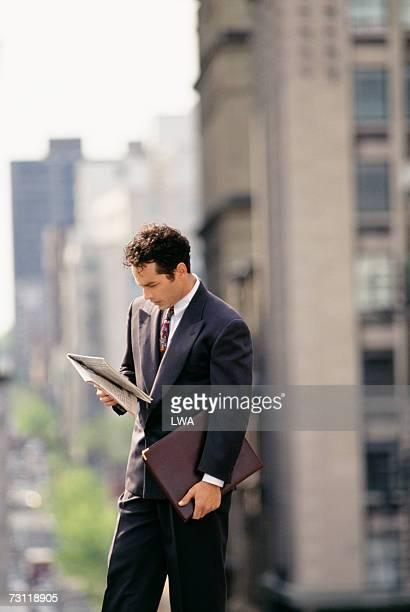 Businessman reading newspaper downtown