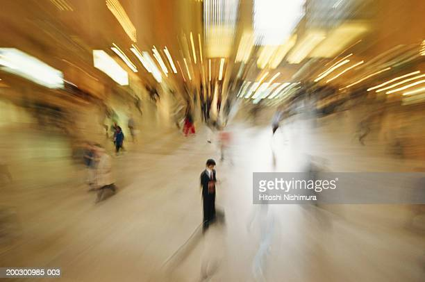 Businessman reading newspaper, elevated view, blurred motion
