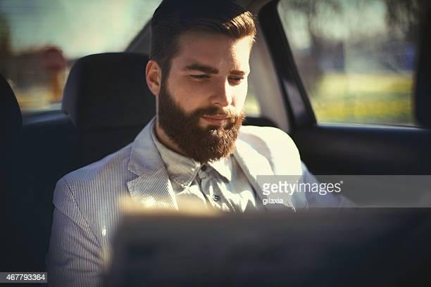 Businessman reading newspaper in a car.