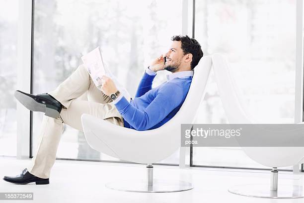 Businessman reading newspaper in armchair and talking on  mobile phone