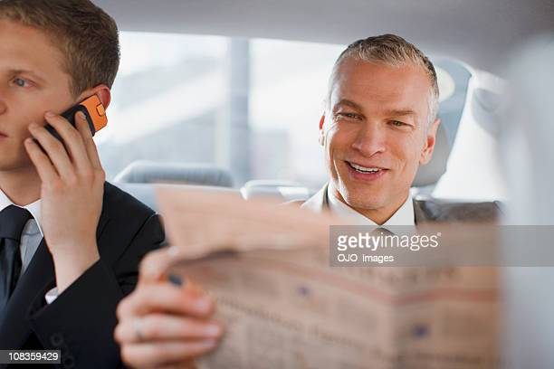 Businessman reading newspaper in back seat of car