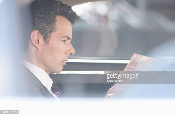 Businessman reading newspaper in backseat of car