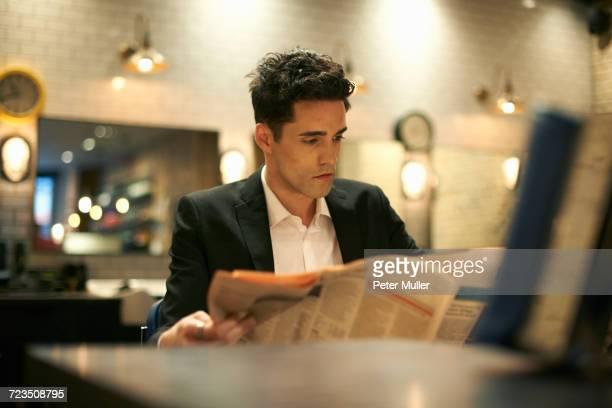 Businessman reading newspaper in barber shop