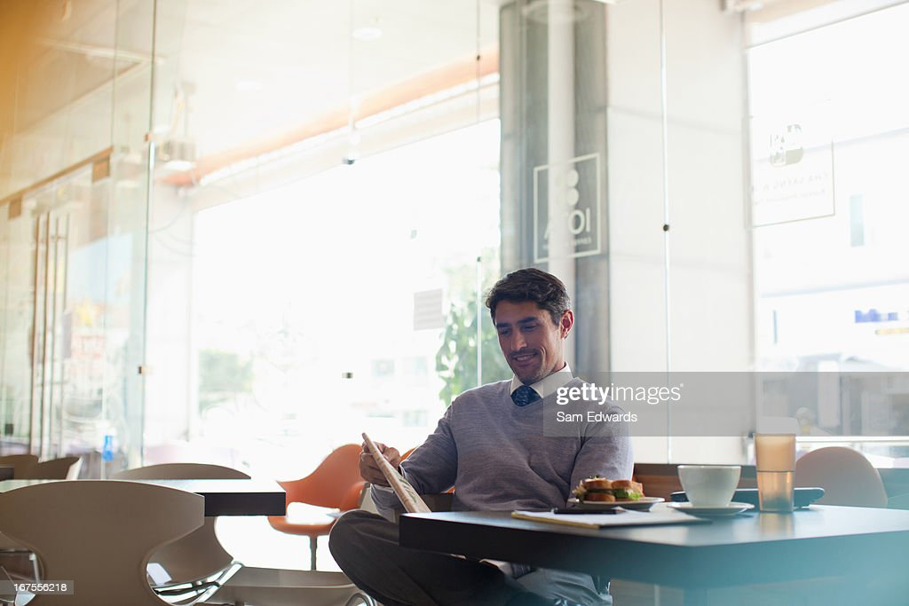 Businessman reading newspaper in cafe : Stock Photo