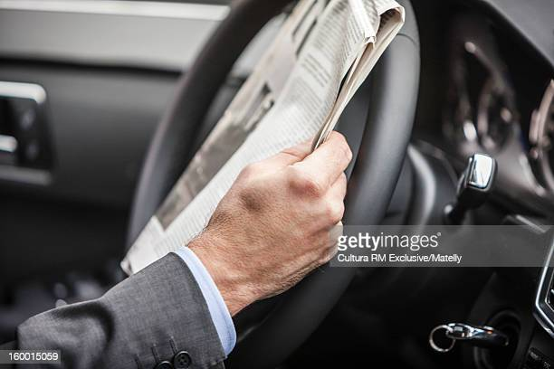 Businessman reading newspaper in car