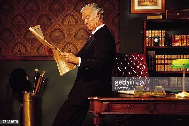 Businessman reading newspaper in elegant office