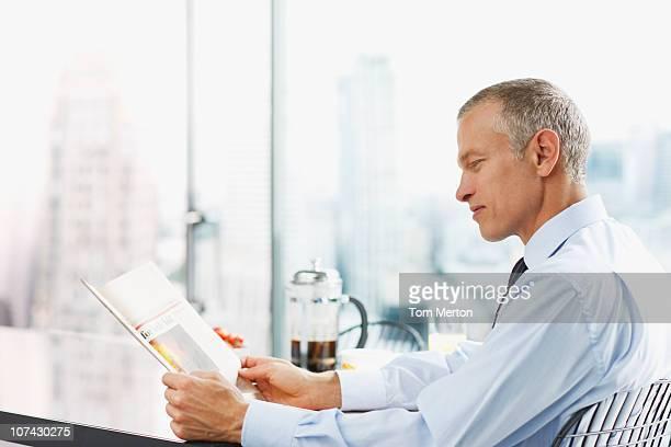 Geschäftsmann liest Zeitung am Morgen