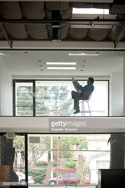 Businessman reading newspaper in office, rear view