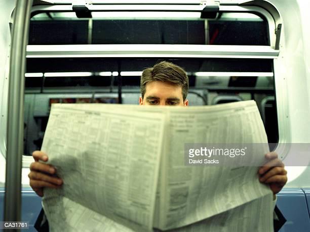 Businessman reading newspaper in subway