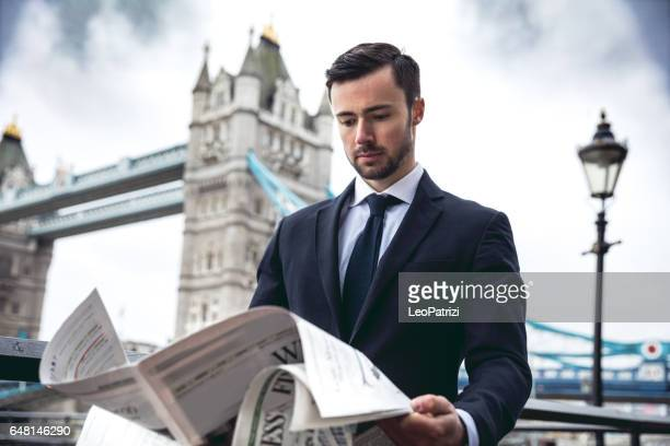 Businessman reading newspaper in the morning in Central London