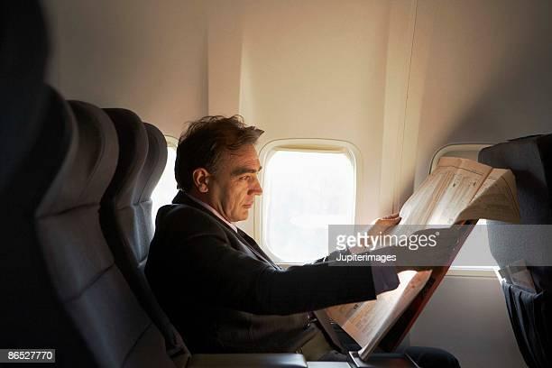 Businessman reading newspaper on airplane