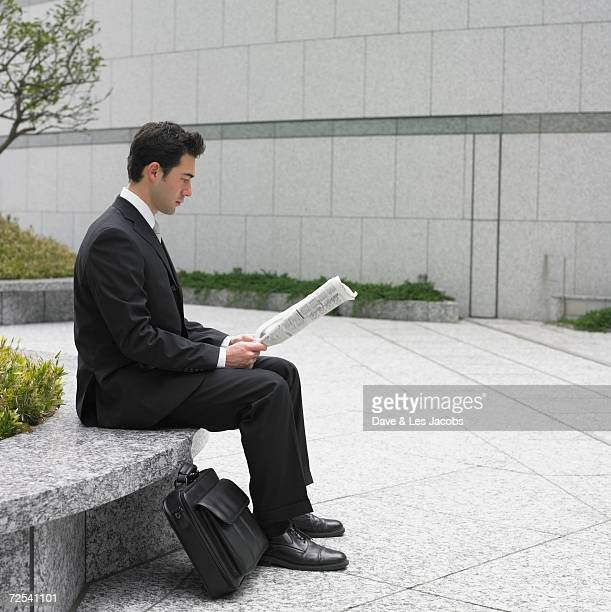 Businessman reading newspaper on bench outdoors
