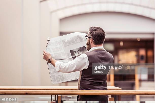 Businessman reading newspaper on office balcony