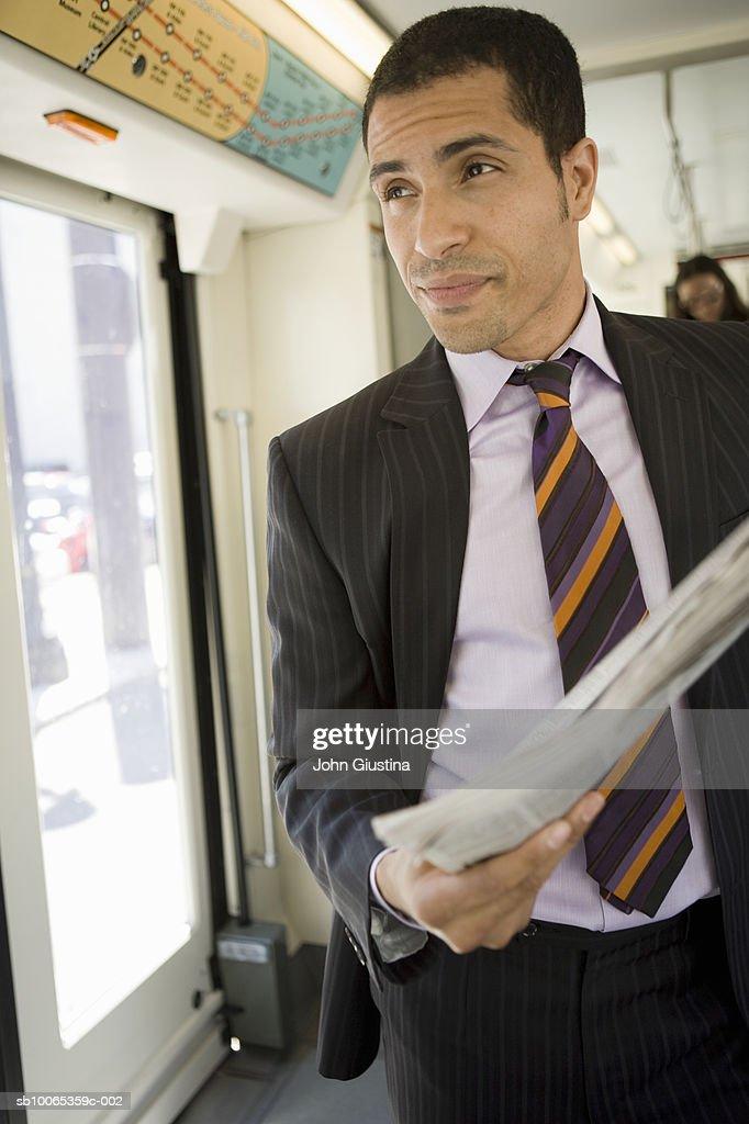 Businessman reading newspaper on tram : Foto stock