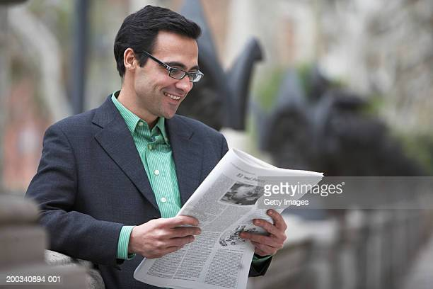 Businessman reading newspaper outdoors, smiling