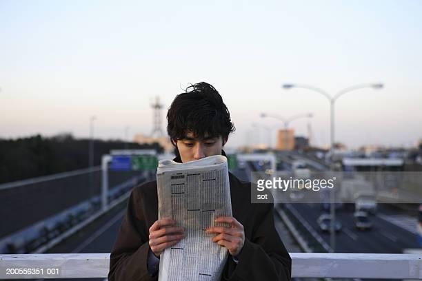 Businessman reading newspaper over highway