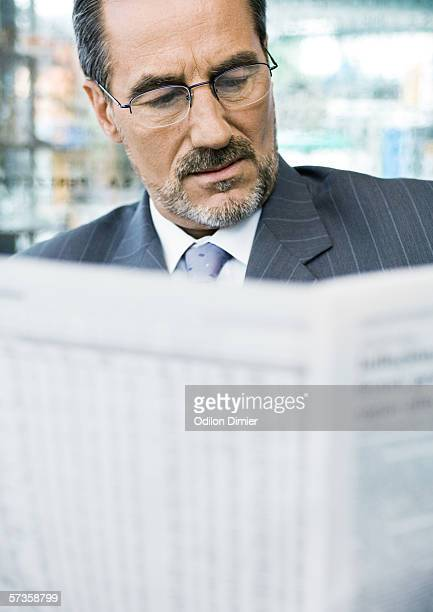 businessman reading newspaper - shareholder stock pictures, royalty-free photos & images