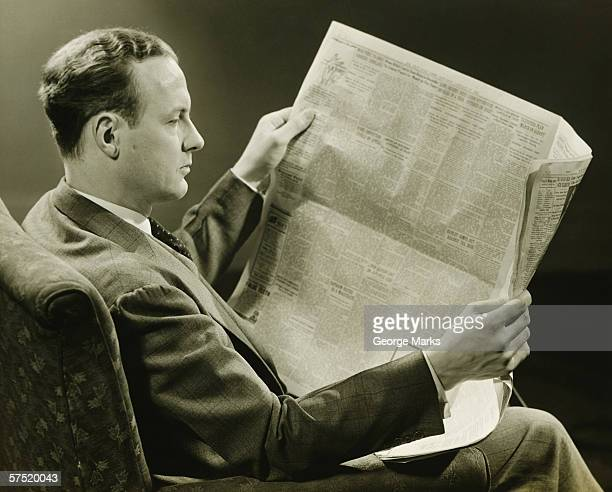 Businessman reading newspaper, (B&W)