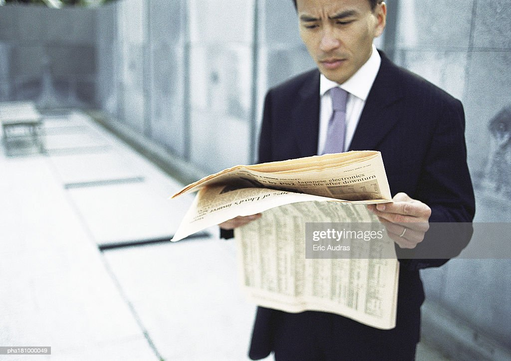 Businessman reading newspaper, waist up, long shot : Stock Photo