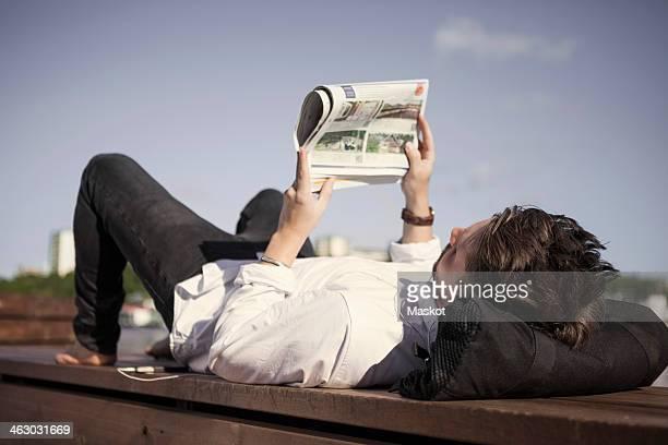 Businessman reading newspaper while lying on boardwalk