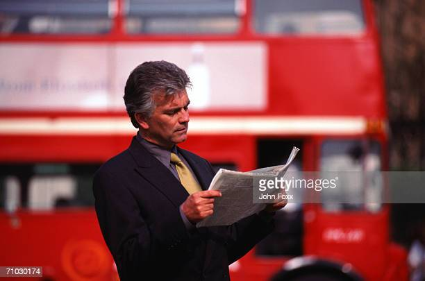 Businessman reading newspaper with bus in background
