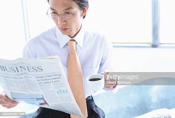 Businessman reading newspaper with cup of coffee