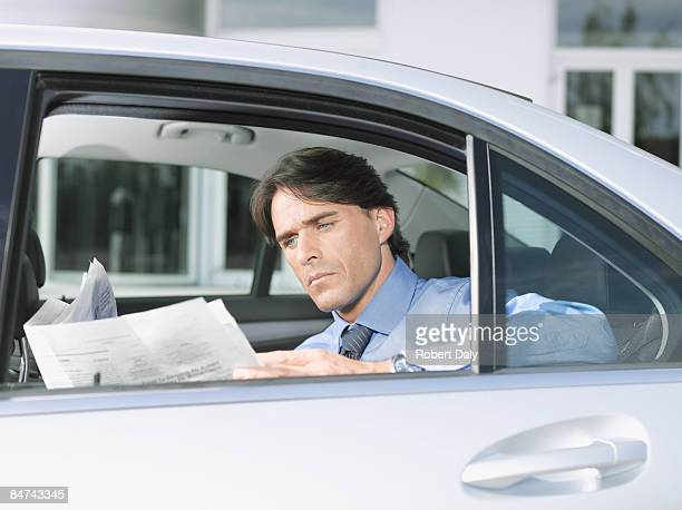 Businessman reading paper in backseat of car
