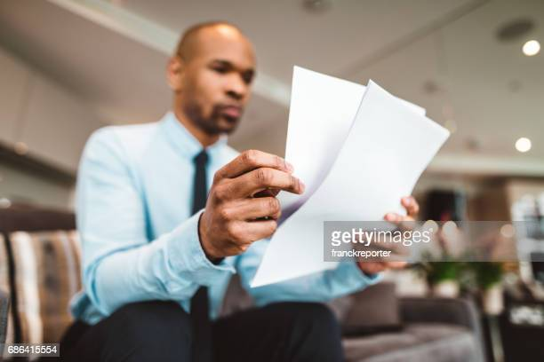 businessman reading rading the bills at home