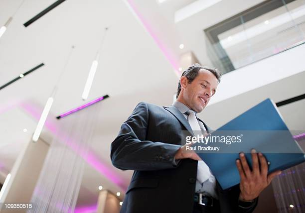 Businessman reading report in lobby