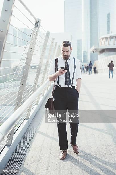 Businessman reading smartphone text update whilst walking on footbridge