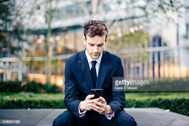 Businessman reading smartphone texts in front of office