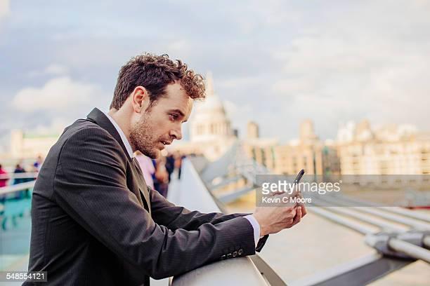 Businessman reading smartphone texts whilst leaning on millennium bridge, London, UK