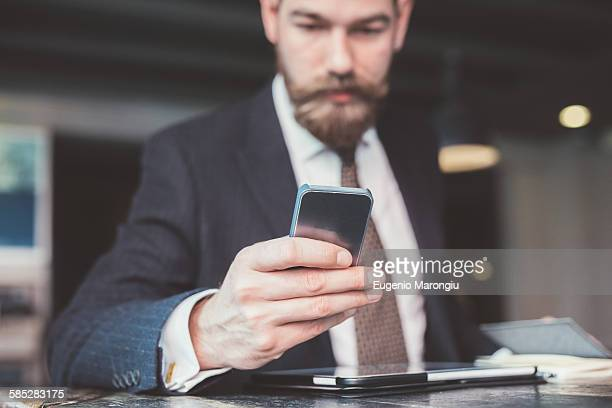 Businessman reading smartphone update at cafe table
