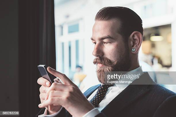 Businessman reading smartphone update in cafe