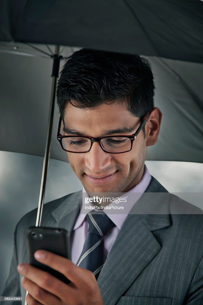 Businessman reading sms on mobile phone : Stock Photo