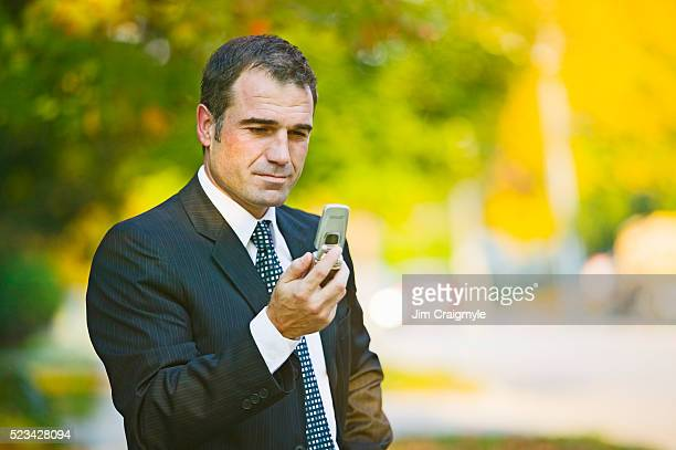 businessman reading text message on cell phone - phone message stock pictures, royalty-free photos & images