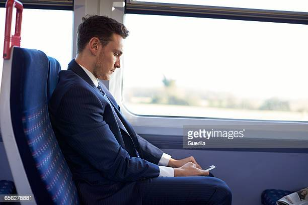 Businessman Reading Text Message On Train During Commute