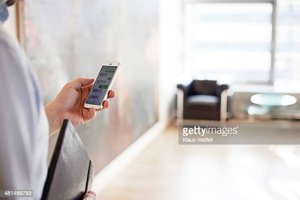 Businessman reading texts on phone, close-up