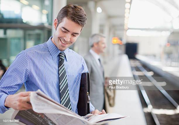 Businessman reading the newspaper on train platform