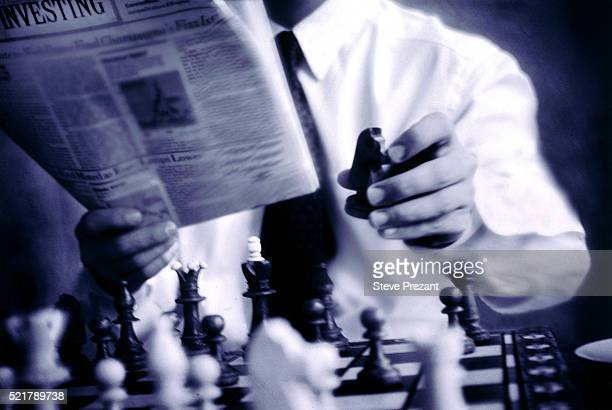 Businessman Reading the Paper and Playing Chess