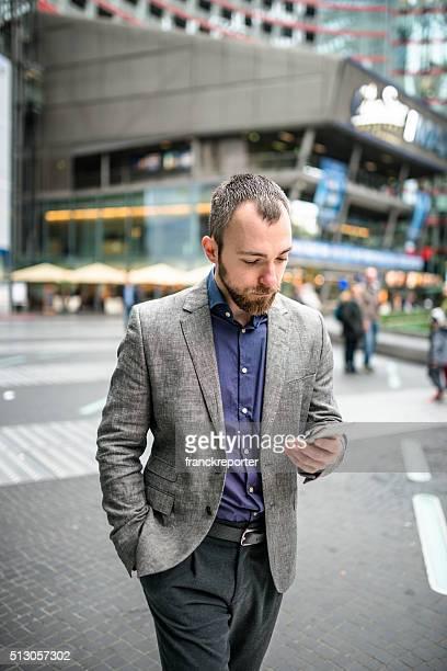 Geschäftsmann Lesen der Smartphone auf der Straße