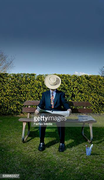 A businessman reads the paper on a park bench with his toothbrush beside him 12 July 2006 AFR Picture by MICHELE MOSSOP